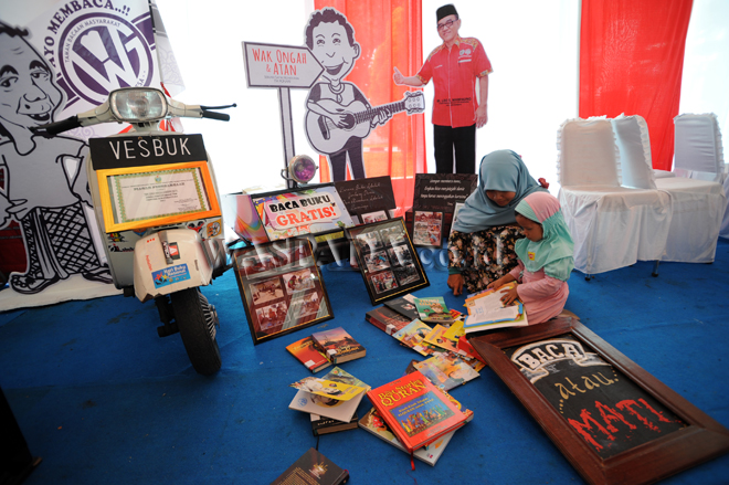 "Sejumlah anak membaca buku yang disediakan ""Vespa Buku (Vesbuk)"" di Perpustakaan daerah Provinsi Sumatera Utara, Medan, Selasa (29/8). Vesbuk yang digagas seorang warga Labuhan Batu, Sumut, dengan konsep berkeliling dan membawa buku bacaan tersebut untuk meningkatkan minat baca warga khususnya anak-anak. (WOL Photo/Ega Ibra)"