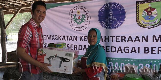 Dosen FE Unimed, Dr. Zulkarnain Siregar, saat menyerahkan bantuan peralatan kepada perwakilan kelompok ibu-ibu Sejati di Desa Nagalawan, akhir pekan lalu. Bantuan tersebut merupakan bagian dari Ipteks Bagi Wilayah (IBW) dengan pembiayaan dari Kemenristekdikti dan difasilitasi LPM Unimed didukung Universitas Medan Area (UMA). (WOL Photo/Ist)