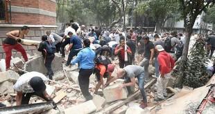 Orang-orang mengangkat puing-puing bangunan yang rusak setelah gempa mengguncang Mexico City pada 19 September 2017 (AFP/ Alfredo Estrella)