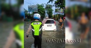 Petugas URC Lantas Pos Diski, Polsek Medan Sunggal, Bripka P Tarigan, mendorong mobil yang mogok akibat terjabak banjir di Jalan dr Mansyur Medan. (WOL. Photo/Gacok).