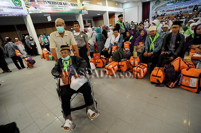 Petugas membantu seorang haji menggunakan kursi roda saat tiba di Asrama Haji, Medan, Kamis (7/9). Sebanyak 391 jamaah haji tiba usai menjalankan ibadah haji di Tanah Suci. (WOL Photo/Ega Ibra)