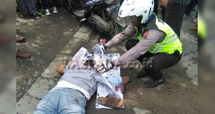 Petugas Lantas Pos Diski, Polsek Medan Sunggal menutupi wajah korban dengan ketas koran.(WOL. Photo/Gacok)