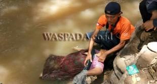 Petugas Inafis Polrestabes Medan melakukan pemeriksaan luar terhadap jenazah nenek hanyut di Sungai Babura. (WOL Photo/Gacok)