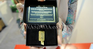 Petugas stan menunjukan emas batangan bermotif batik produksi PT Aneka Tambang (ANTAM) yang dipamerkan, Medan, Sabtu (7/10).  Emas batangan bermotif batik tersebut dibanderol dengan harga Rp. 6.286.070 untuk ukuran 10 gram dan Rp. 12.123.135 untuk ukuran 20 gram, serta tersedia empat pilihan motif batik nusantara yaitu  motif Karang Picis, Mega Mendung, Sida Mukti dan Parang Barong. (WOL Photo/Ega Ibra)