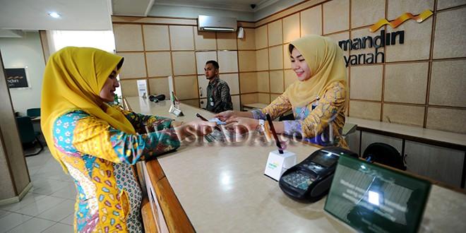 Petugas teller bank memakai pakaian batik saat melayani nasabah, Medan, Senin (2/10). Dalam rangka Hari Batik Nasional, Bank Mandiri Syariah mewajibkan seluruh karyawannya untuk memakai pakaian batik saat melayani nasabah. (WOL Photo/Ega Ibra)