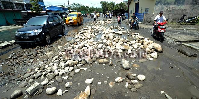 Pengendara menghindari jalan yang rusak dan tumpukan batu di kawasan jalan Yos Sudarso, Medan, Kamis (5/10). Jalan rusak dan tumpukan batu di kawasan tersebut dapat membahayakan pengendara yag melintas. (WOL Photo/Ega Ibra)