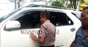 Petugas Sentra Pelayanan Kepolisian Terpadu (SPKT ) Polsek Medan Sunggal melihat mobil korban pecah kaca maling.(WOL. Photo/Gacok).