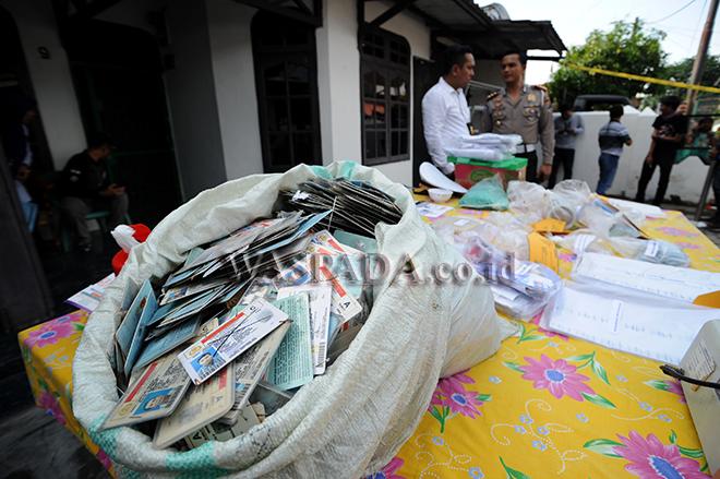 Petugas kepolisian berjaga di dekat barang bukti Surat Izin Mengemudi (SIM) palsu saat gelar kasus pembuatan SIM palsu, di Medan, Sabtu (30/9). Pihak kepolisian Polda Sumatera Utara menangkap tiga orang tersangka pembuatan SIM palsu yang satu diantaranya merupakan anggota kepolisian dengan barang bukti jutaan SIM yang telah habis masa berlakunya, 33 SIM palsu siap edar dan 46 SIM palsu yang telah diedarkan. (WOL Photo/Ega Ibra)