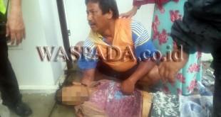 Tukirin (47) menangis terisak-isak sambil memeluk abangnya Paidi tewas saat buang sampah.(WOL Photo/Gacok)
