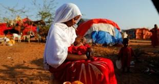 Zeinab (14) duduk menggendong keponakannya di kamp bagi warga yang mengungsi karena kekeringan yang melanda wilayah Dollow, Somalia, Selasa (4/4). (REUTERS/Zohra Bensemra/djo/17)