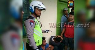 Petugas URC Lantas Pos Diski, Polsek Medan Sunggal, Bripka Pol P Tarigan SH, memperlihatkan kunci silang tiga dan disaksikan dua pelaku dengan posisi jongkok di lokasi penangkapan.(WOL Photo/Gacok)