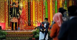 Presiden Joko Widodo (kanan) memakai sepatu saat prosesi Ngunduh Mantu pernikahan putri Presiden dan menantunya Kahiyang Ayu - Bobby Nasution, di Medan, Sabtu (25/11). Resepsi tersebut dilaksanakan dengan prosesi upacara adat perkawinan Mandailing seperti pemukulan Gondang Sambilan, Manortor, Tapian Raya Na Martua, Mangupa, Ajar Poda, Tortor Somba dan Manyoda Gondang. (WOL Photo/Ega Ibra)