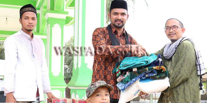 Iskandar Usman Alfarlaky menyerahkan bantuan untuk korban kebakaran 13 rumah dewan guru di Dayah Bustanul Huda Paya Pasi, Kecamatan Julok,Aceh Timur, Selasa (7/11). (WOL Photo)