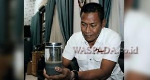 Kapolres Aceh Utara, AKBP Ir Untung Sangaji, menunjukkan salah satu contoh air mineral buatannya sendiri. (WOL Photo/Chairul Sya'ban)