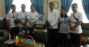 Bupati Nias Barat Faduhusi Daely menerima secara simbolis tong sampah dari KMN Komisariat UPMI Medan. Istimewa