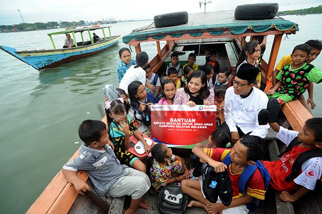 ACS Humas Pelindo 1, Fiona Sari Utami berbicara dengan sejumlah anak-anak yang tinggal di Kampung Nelayan Belawan saat membagikan sepatu, Belawan, Medan, Jumat (29/12). PT Pelindo 1 membagikan 50 pasang sepatu kepada anak-anak yang tinggal di Kampung Nelayan sebagai bentuk kepedulian terhadap kondisi masyarakat, khususnya yang berada di sekitar wilayah kerja PT Pelindo 1. (WOL PHOTO/Ega Ibra)