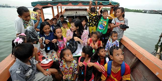 ACS Humas Pelindo 1, Fiona Sari Utami berbicara dengan sejumlah anak-anak yang tinggal di Kampung Nelayan Belawan saat membagikan sepatu, Belawan, Medan, Jumat (29/12). PT Pelindo 1 membagikan 50 pasang sepatu sekolah kepada anak-anak yang tinggal di Kampung Nelayan sebagai bentuk kepedulian terhadap kondisi masyarakat, khususnya yang berada di sekitar wilayah kerja PT Pelindo 1. (WOL PHOTO/Ega Ibra)