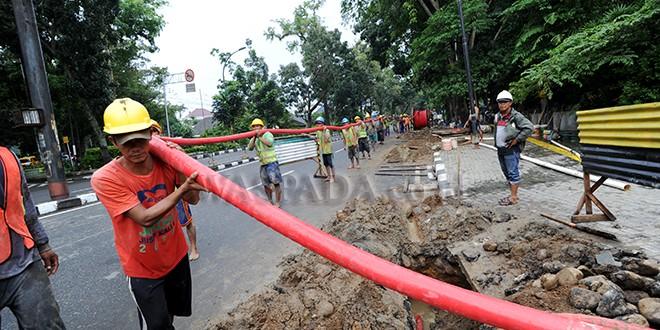 Pekerja mengangkat kabel di dekat proyek galian PLN kawasan jalan Jenderal Sudirman, Medan, Kamis (28/12). Proyek tersebut merupakan pengerjaan galian PLN Area Medan untuk Saluran Kabel Tegangan Menengah (SKTM) 20 KV. (WOL Photo/Ega Ibra)
