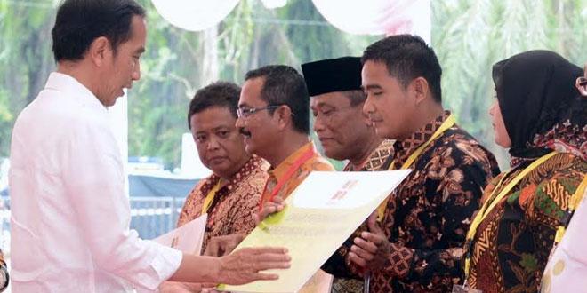 Koperasi Anugerah Jaya Mandiri Sejahtera (AJMS) Desa Perlabian, Akmad Rizaldi Syah, menerima dana hibah peremajaan sawit rakyat dari Presiden Jokowi, baru-baru ini. (WOL Photo/Ist)