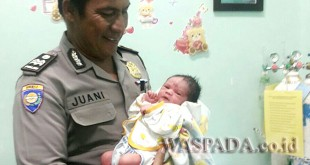 Petugas Babinkamtibmas Polsek Medan Baru Aiptu Juani, menggendong bayi ibu yang melahirkan di depan Hotel Merlin, Jalan Gatot Subroto Medan. (WOL. Photo/Gacok).