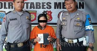 Petugas SPKT dan Provost Polsek Medan Sunggal mengapit tersangka wanita spesialis pencuri tas usai interogasi, Minggu (24/12). (WOL Photo/gacok)