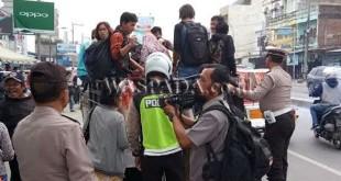 Petugas Lantas dibantu Sabhara menaikkan penumpang ke truk. (WOL Photo/Gacok)