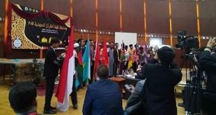 Lauhin Mahfudz mewakili Indonesia memegang bendera Merah Putih, bersama 20 peserta lainnya dari berbagai negara, saat Pembukaan MTQ Internasional di Kairo, Mesir, Jum'at (23/3) waktu setempat. (Istimewa)