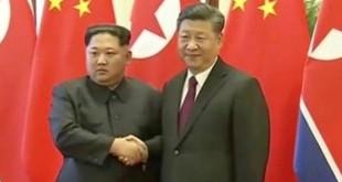 Pemimpin Korea Utara Kim Jong-un berjabat tangan dengan Presiden China Xi Jinping dalam foto yang diambil dari video yang dirilis pada 28 Maret 2018. (Foto: CCTV/Reuters)