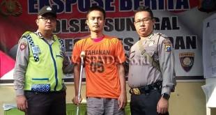 Penyidik pembantu (juru periksa) didampingi petugas Sabhara Polsek Medan Sunggal memapah tersangka curanmor, kakinya patah diamuk massa.(WOL Photo/Gacok)