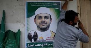 Seorang pria memasang poster Fadi al-Batsh yang tewas dibunuh di Malaysia di rumah keluarganya di Gaza. (Foto: Reuters)