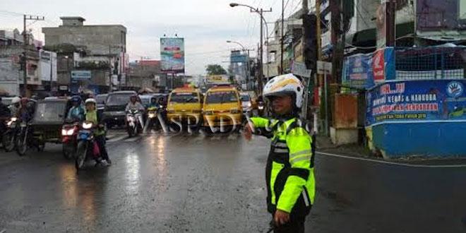 Petugas Lantas Polsek Medan Sunggal, Aipda P Tarigan, tampak memakai jaket dan helm mengatur arus lalu lintas saat guyuran hujan deras di persimpangan empat Pinang Baris. (WOL Photo/Gacok)