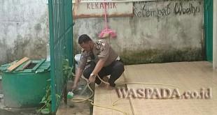 Kanit Lantas Polsek Medan Sunggal, Iptu Syahri Ramadhan SH membersihkan lokasi Masjid Jamik di Jalan Pinang Baris Medan.(WOL. Photo/Gacok)
