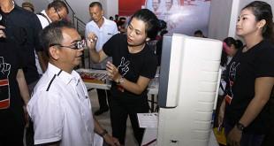 Calon Wakil Gubernur Sumut, Sihar Sitorus mencoba menggunakan alat periksa mata digital dan periksa kesehatan dalam kegiatan pengobatan gratis di acara Bara Baja Djoss, di Medan, Minggu  (20/5). (WOL Photo/Ist)