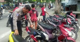 Kanit Lantas Polsek Medan Sunggal, Iptu Syahri Ranadhan SH, mengecek jenis kendaraan dan nomor mesin serta rangka untuk keabsahan kendaraan tersebut. (WOL Photo/Gacok)